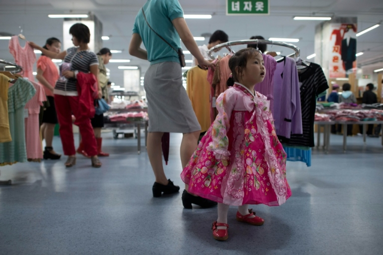 <p>A North Korean girl wearing traditional dress stands at a clothing section inside a high-end supermarket in Pyongyang on July 28, 2013.</p>