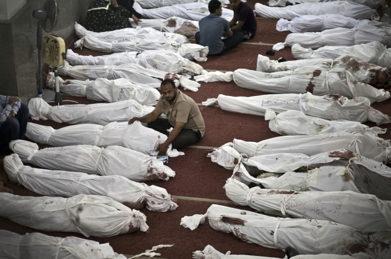 <p>Egyptians mourn over bodies wrapped in shrouds at a mosque in Cairo on August 15, 2013, following a crackdown on the protest camps of supporters of ousted Islamist president Mohamed Morsi the previous day.</p>