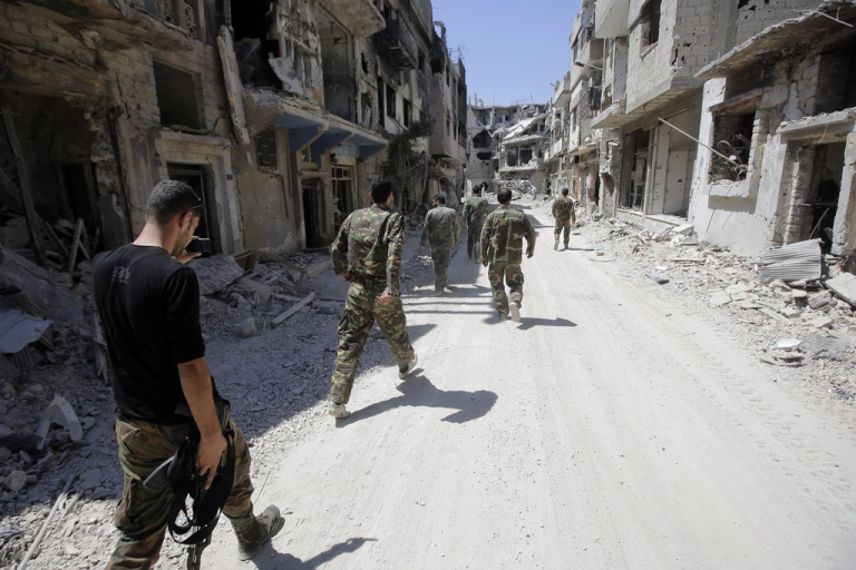 <p>Soldiers of the Syrian government forces patrol in a devastated street on July 31, 2013 in the district of al-Khalidiyah in the central Syrian city of Homs. The Syrian government announced the capture of Khalidiyah, a key rebel district in Homs, Syria's third city and a symbol of the revolt against President Bashar al-Assad.</p>