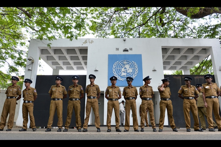 <p>Sri Lankan police officials stand guard outside the United Nations office in Colombo on Aug. 26, 2013, during a demonstration by 'Power of Ravana' Buddhist monks denouncing UN human rights chief Navi Pillay on the first full day of her visit to Sri Lanka.</p>