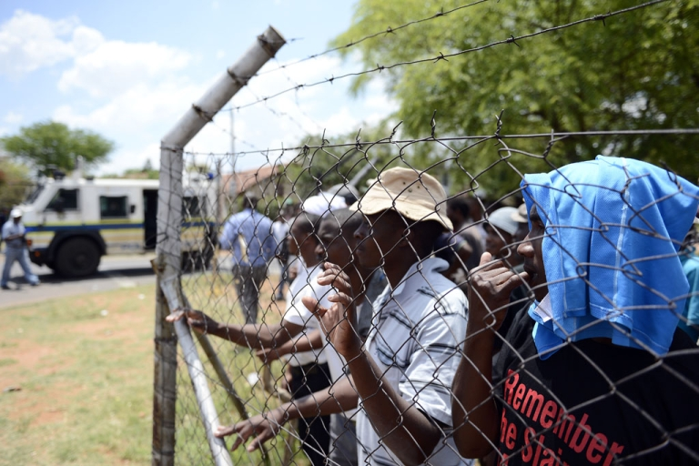 <p>Striking miners look through a fence at riot police at a rally organized by the Congress of South African Trade Unions in Rustenburg, northwest of Johannesburg, on October 27, 2012. South African gold mines are again bracing for strikes, officials said on Aug. 28, 2013.</p>