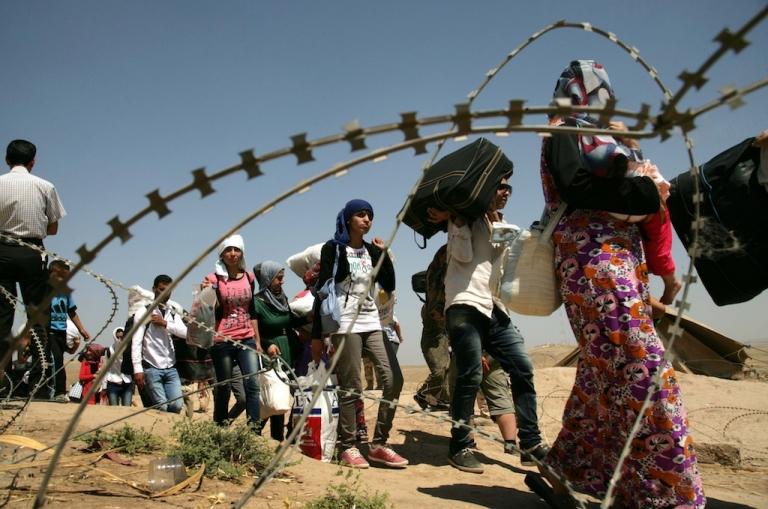 <p>Syrian refugees cross the border into the autonomous Kurdish region of northern Iraq, on Aug. 18, 2013.</p>