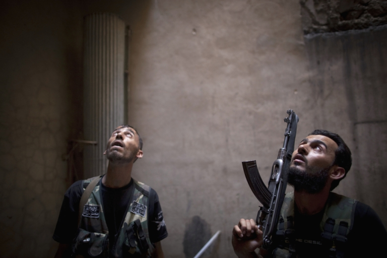 <p>Rebel fighters look up listening as they take positions during clashes with pro-government forces in the Salaheddine district of the northern Syrian city of Aleppo, on July 9, 2013.</p>