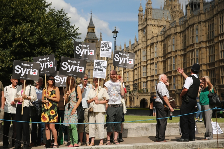 <p>Anti-war protesters gather on College Green outside the Houses of Parliament on Aug. 29, in London, England. Lawmakers there voted against plans for a UK military response to chemical weapons attack in Syria.</p>