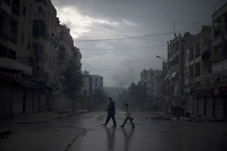 <p>A father and son return home with vegetables, as smoke from a pro-government forces artillery strike ascends in the background, in the al-Amaria neighborhood in the city of Aleppo, on Jan. 6, 2013.</p>