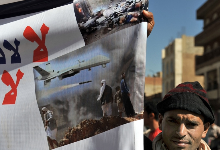 <p>A Yemeni man holds a banner during a protest against United States drone strikes on Yemen close to the home of Yemeni President Abdrabuh Mansur Hadi, in the capital Sana'a, on Jan. 28, 2013.</p>