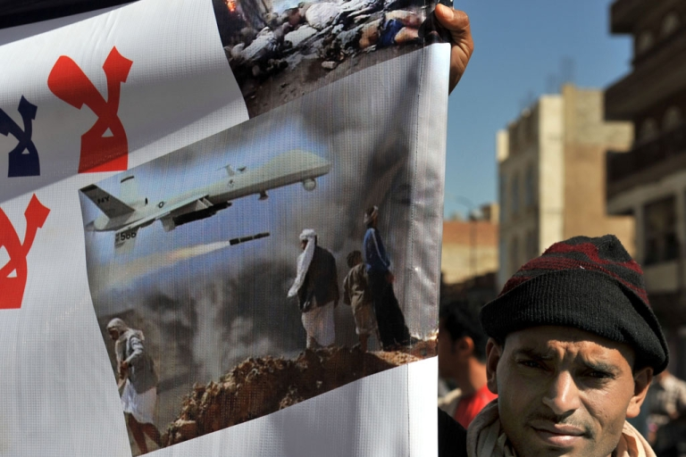 <p>A man holds a banner protesting US drone attacks on Yemen near Yemeni President Abdrabuh Mansur Hadi in the capital Sanaa on January 28, 2013.</p>