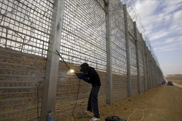 <p>A laborer works at the construction site of the fence along Israel's border with Egypt near the Red Sea resort town of Eilat on Feb. 15, 2012. The barrier along the 150-mile border with the Egyptian Sinai was completed in late 2013.</p>