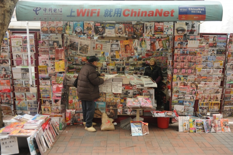 <p>A newspaper vendor (R) talks to a customer at her booth on a street in Shanghai on Jan. 8, 2013. In December, China announced that it would expel dozens of foreign reporters from the country, in an unprecedented crackdown by authorities against foreign news organizations.</p>