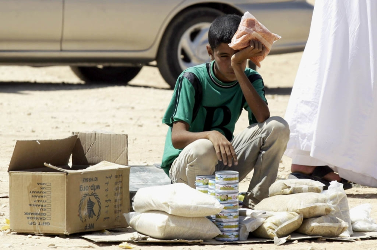 <p>A young Syrian refugee boy sells canned tuna and other food items in the Zaatari refugee camp, located close to the Jordanian city of Mafraq, near the border with Syria, on September 4, 2013.</p>