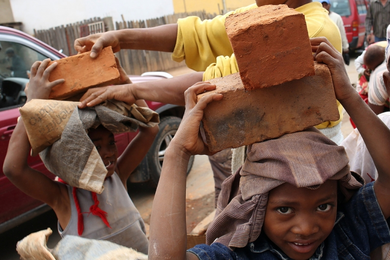 <p>Children carry bricks on December 19, 2013 in Antananarivo, ahead of the upcoming presidential election.</p>