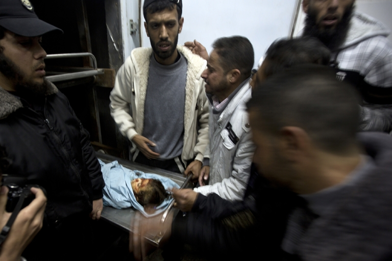 <p>A relative of three-year-old Palestinian girl Hala Abu Sabikha identifies her as she lies in the morgue of a hospital in Deir al-Balah in the central Gaza Strip on December 24, 2013.</p>