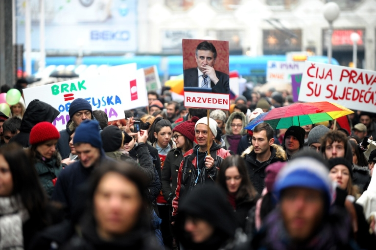 <p>Croatian gay rights supporters hold a picture of Tomislav Karamarko, leader of the conservative opposition Croatian Democratic Union party, reading 'Divorced' as they gather for a protest in Zagreb on November 30, 2013 on the eve of a constitutional referendum that could outlaw same-sex marriage in the EU's newest member state.</p>