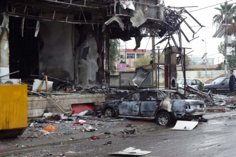 <p>A picture taken on December 5, 2013 shows damages and a burnt vehicle after the mall in the northern Iraqi city of Kirkuk was stormed by security forces to end an hours-long siege that has followed an attack involving a car bomb, gunmen and would-be suicide bombers.</p>