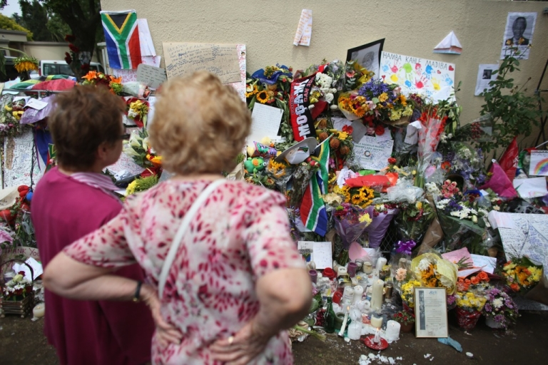 <p>Well-wishers pay their respects outside the Houghton home of the former South African President Nelson Mandela on December 9, 2013 in Johannesburg, South Africa.</p>