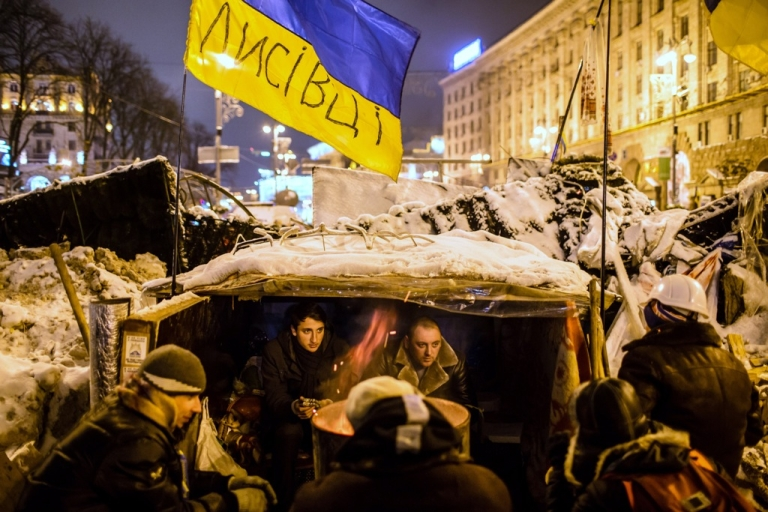 <p>Ukrainian anti-government protesters hunker down in a makeshift shelter built into a barricade near Kyiv's Independence Square on December 11, 2013.</p>