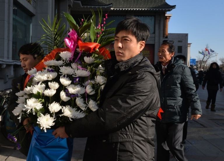 <p>North Koreans take flowers to the North Korean Consulate in the Chinese border town of Dandong to pay their respects on the second anniversary of the death of former leader Kim Jong Il, on December 17, 2013.</p>
