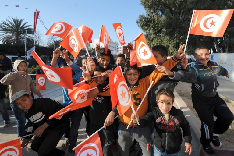 <p>Tunisian children wave the national flag as they gather to mark the third anniversary of the uprising that toppled deposed president Zine El Abidine Ben Ali in Sidi Bouzid's Mohamed Bouazizi square on December 17, 2013. The square was named after the fruit seller whose self-immolation sparked the revolution that ousted the long-standing dictator and ignited the Arab Spring.</p>