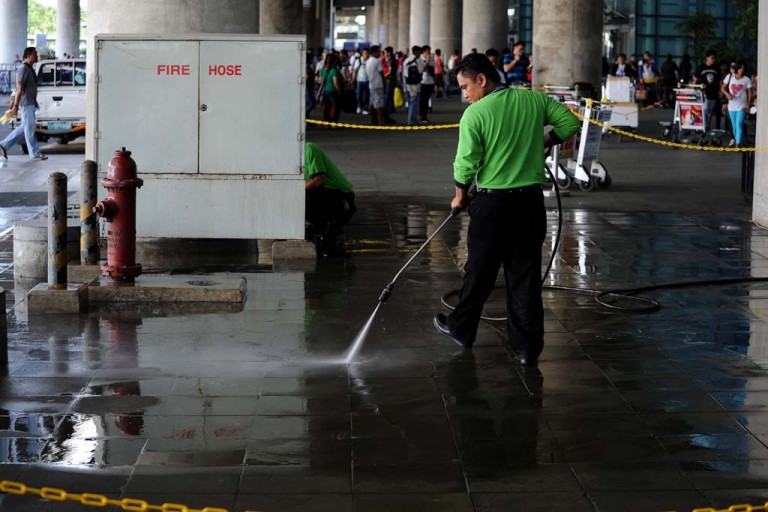 <p>A maintenance crew worker cleans the crime scene after gunmen opened fire outside the Manila International Airport in Manila on December 20, 2013.</p>
