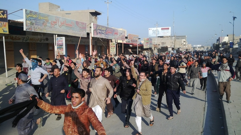 <p>Iraqis march during a protest against the arrest of MP Ahmed al-Alwani in Ramadi, west of Baghdad, on December 28, 2013.</p>