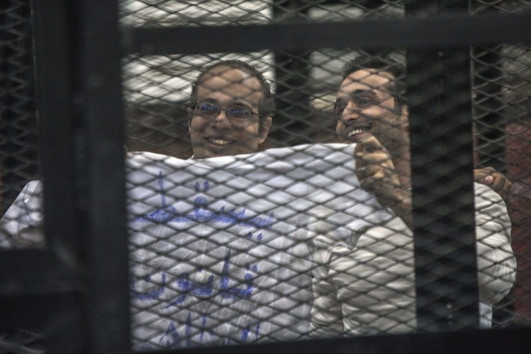 <p>Political activist and coordinator of the April 6 Movement, Ahmed Maher and activist Ahmed Doma (R) show a T-shirt reading 'Dropping the law on demonstrations' during his trial on Dec. 8, 2013 in Cairo, Egypt.</p>