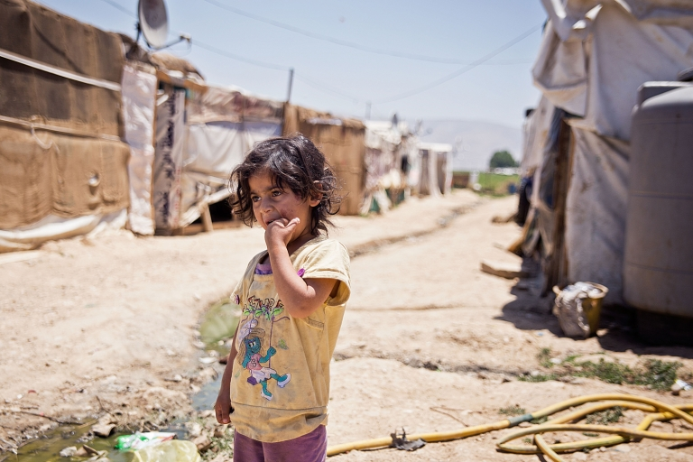 <p>A Syrian girl stands between two rows of shacks in an informal refugee camp in the central Bekaa Valley of Lebanon.</p>