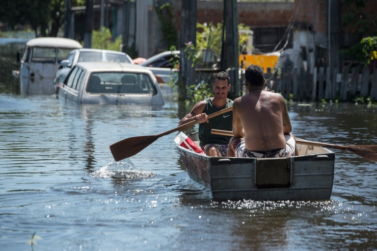<p>Men row in a boat along a flooded street in Vila Velha, Espirito Santo state, Brazil, on December 27, 2013.</p>