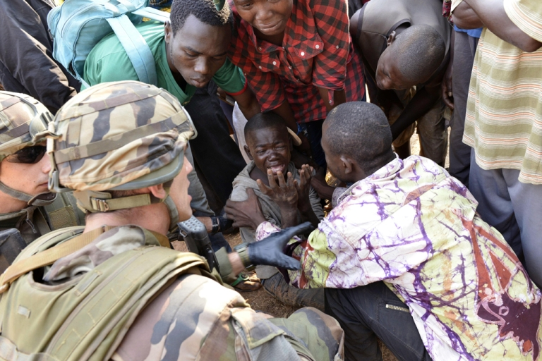 <p>French troops of the Sangaris operation and civilians try to comfort a boy crying after a demonstrator was shot dead near the international airport in Bangui on December 23, 2013.</p>