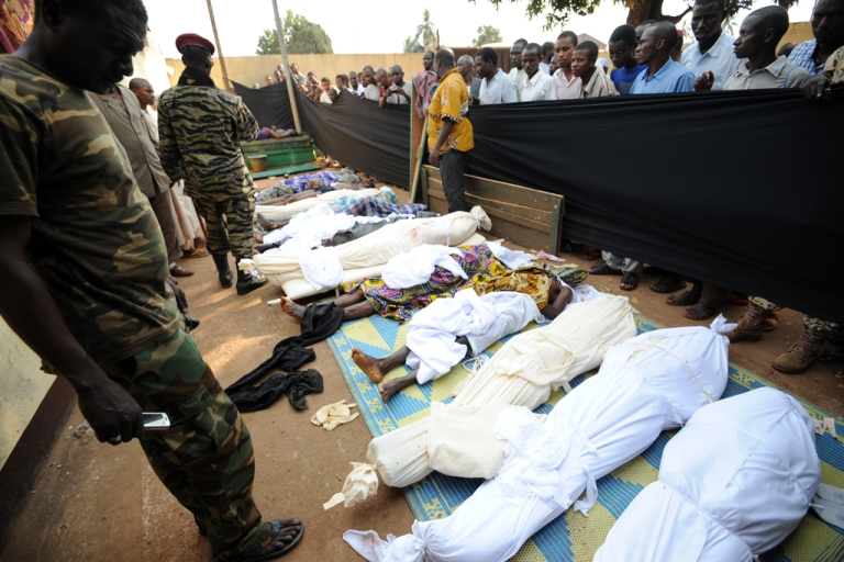<p>People stand near bodies found lying in a mosque and in its surrounding streets in the Central African capital Bangui on December 5, 2013, after overnight violence.</p>
