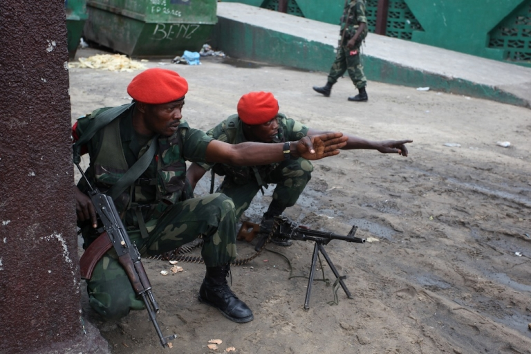 <p>Military police gesture near the state broadcaster RTNC as gunfire erupted on Dec. 30, 2013 at the premises of the broadcaster in Kinshasa.</p>