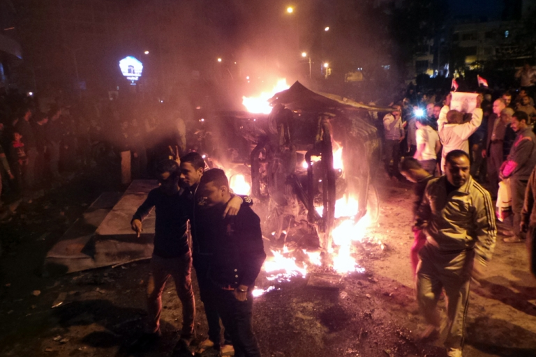 <p>Angry Egyptians set fire to a microbus, said to be belong to a company owned by a businessman who supports the Muslim Brotherhood on December 24, 2013.</p>