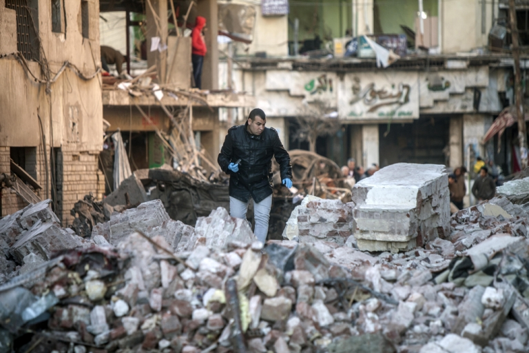 <p>Egyptian security forces inspect the site of a powerful car bomb explosion in the Egyptian city of Mansura, North of Cairo, on December 24, 2013.</p>