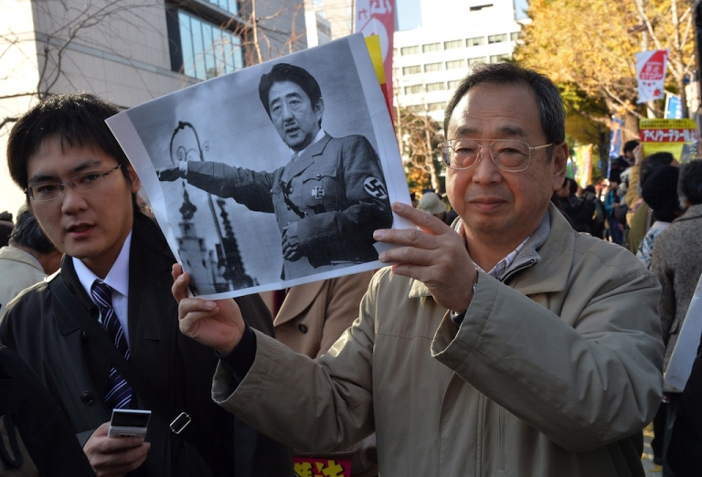 <p>A civic group member holds a picture of Japanese Prime Minister Shinzo Abe morphed with the image of former German chancellor Adolf Hitler during a rally to protest against a controversial new state secrets bill in front of the National Diet in Tokyo on December 6, 2013.  A controversial state secrets bill became law in Japan Friday night despite objections from a broadening coalition who say the legislation is being rushed through parliament.</p>