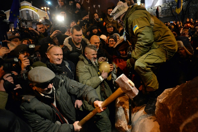 <p>A protester breaks apart a statue of Lenin at a monument in his honor after it was pulled down during a mass rally called