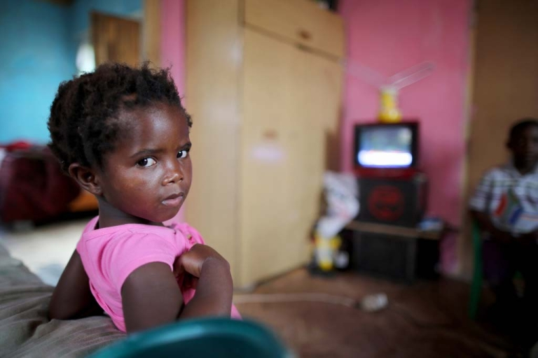 <p>A young girl watches the televised funeral of former South African President Nelson Mandela in his home village of Qunu on Dec. 15, 2013.</p>