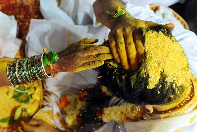 <p>An Indian bride and groom smear yellow rice - Talambralu - on their heads during a mass wedding ceremony in 2009.  Many Indians consider their wedding day the most important of their life. A matchmaking service helps HIV+ people who want to get married.</p>