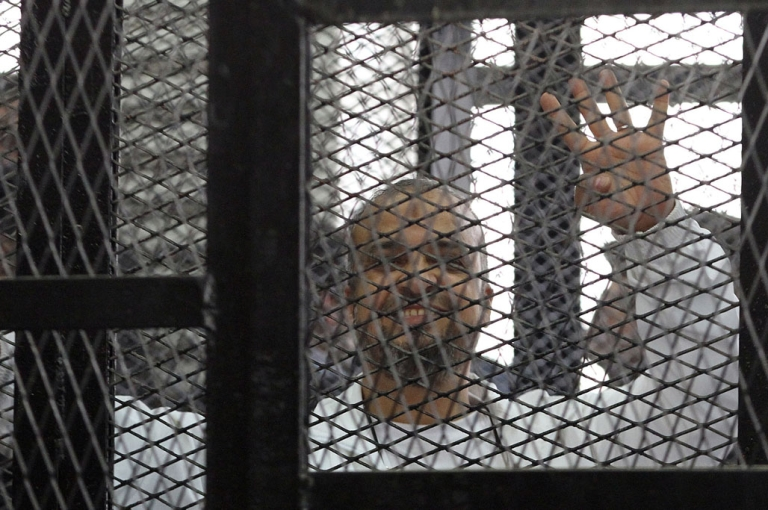 <p>Muslim Brotherhood member Mohamed Beltagy holds up four fingers, called rabaa (four) in Arabic, from the defendants' dock in a Cairo courtroom December 11, 2013. The trial of Egypt's Muslim Brotherhood chief Mohamed Badie and his deputies came to an abrupt end when judges walked out, citing chaos in the dock.</p>