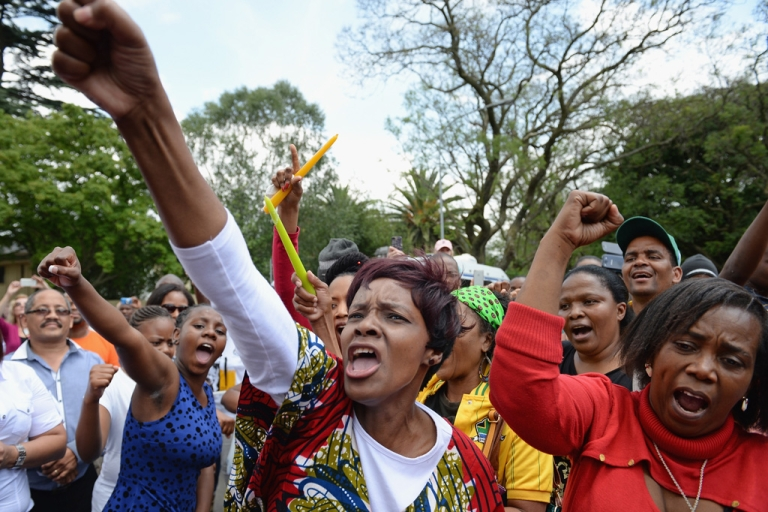 <p>South Africans gather to pay tribute to former President Nelson Mandela outside his Houghton home on Dec. 7, 2013 in Johannesburg.</p>