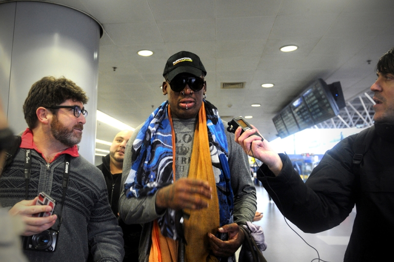 <p>Former US NBA basketball player Dennis Rodman (C) speaks to members of the media as he makes his way through Beijing's international airport on December 19, 2013.  Rodman is on a visit to North Korea from December 19 to 23.</p>