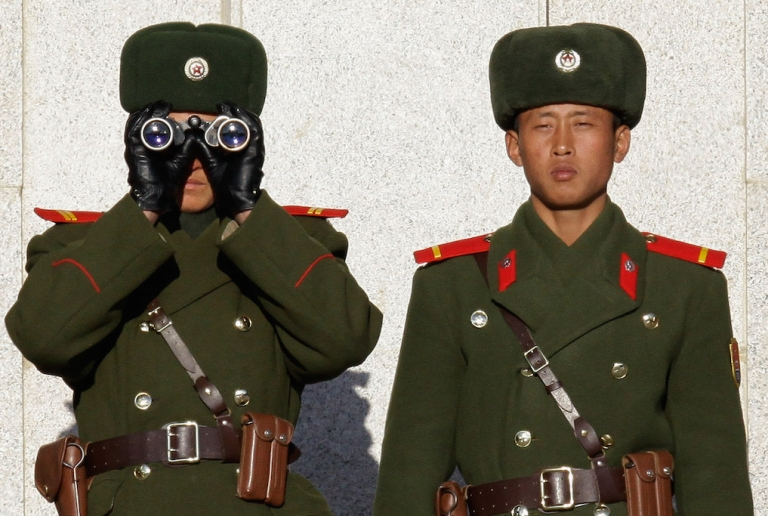 <p>North Korean soldiers look at South Korea across the Korean Demilitarized Zone (DMZ), in December 2011.</p>