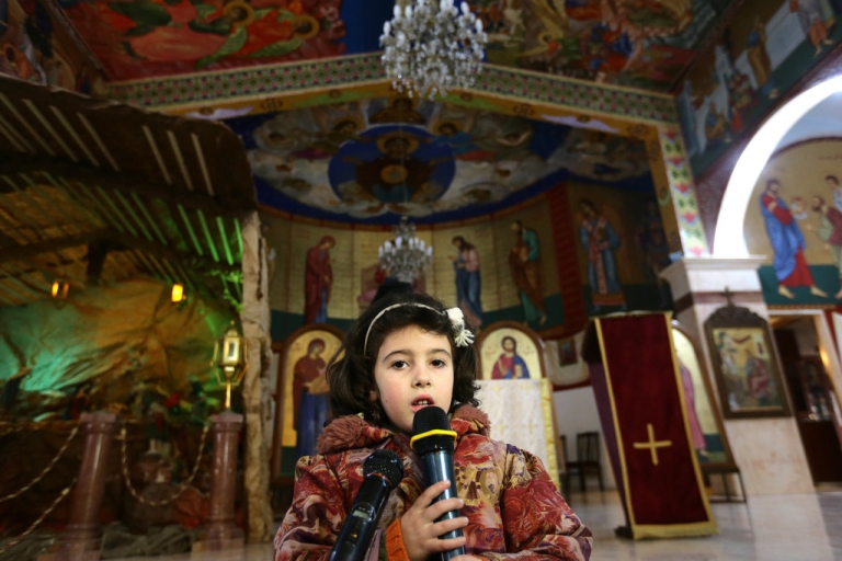 <p>A Syrian girl from the Christian town of Maalula, a symbol of the ancient Christian presence in Syria which is currently under control of Syrian rebels, including jihadist groups, speaks during a service at the St. Joseph church in Damascus, on December 18, 2013. Syrian Melkite Greek Catholic Patriarch Gregory III Laham, has called on his fellow Christians to stay in Syria, despite the brutal conflict raging in the country. According to the patriarch, 450,000 Syrian Christians have been displaced by the conflict that began in March 2011, around 40,000 of whom have fled to Lebanon.</p>