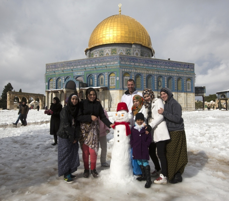 <p>Palestinians pose for a photograph next to a snowman in front of the Dome of the Rock at the Al-Aqsa mosque compound in the Old City of Jerusalem on Dec. 13, 2013.</p>