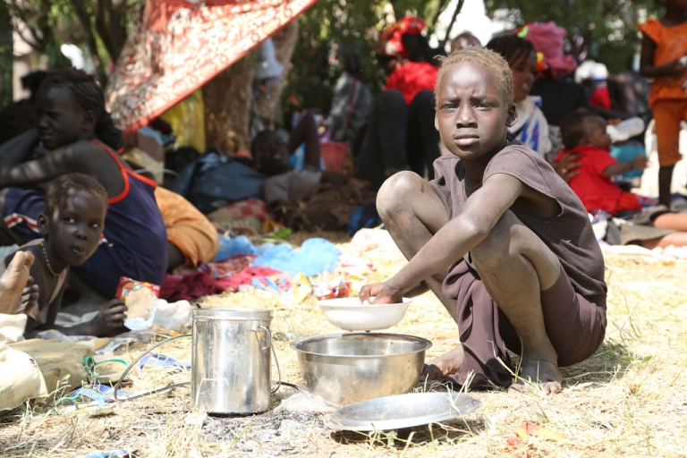 <p>A young girl displaced following recent fighting in Juba, South Sudan, prepares a meal inside the UNMISS compound on December 17, 2013 on the outskirts of the capital.</p>