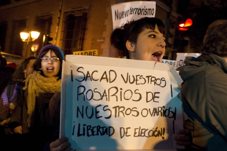 <p>A woman holds a placard reading