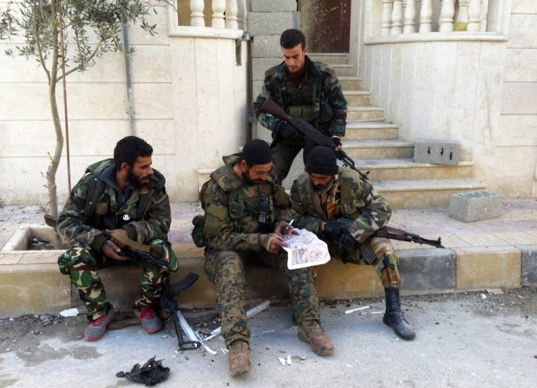 <p>Syrian pro-government forces read a map in the town of Nabak near Damascus on December 7, 2013, as the regime has been battling rebel forces to gain control of a string of strategic towns and villages along the Damascus-Homs highway, north of the capital. Government forces are seeking to encircle the rebels in the Qalamoun region north of Damascus and sever opposition supply lines across the nearby border with Lebanon.   AFP PHOTO/SAM SKAINE        (Photo credit should read SAM SKAINE/AFP/Getty Images)</p>