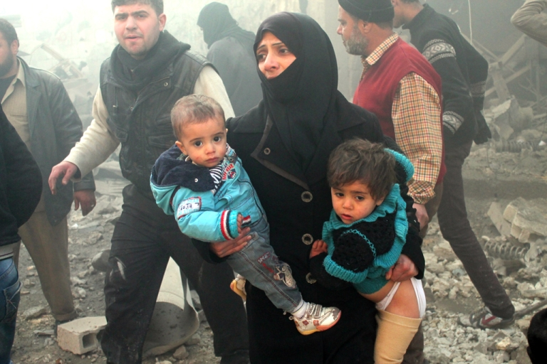 <p>A Syrian woman carries children following airstrikes on a rebel area of the war-torn northern city of Aleppo on December 15, 2013.</p>