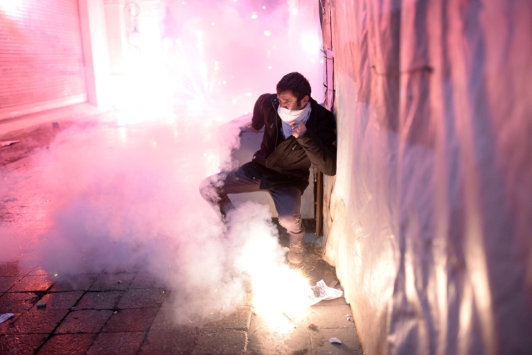 <p>A Turkish protestor protects himself as fireworks explode on the Istiklal Avenue on December 27, 2013, during clashes between the Turkish police and protestors.</p>