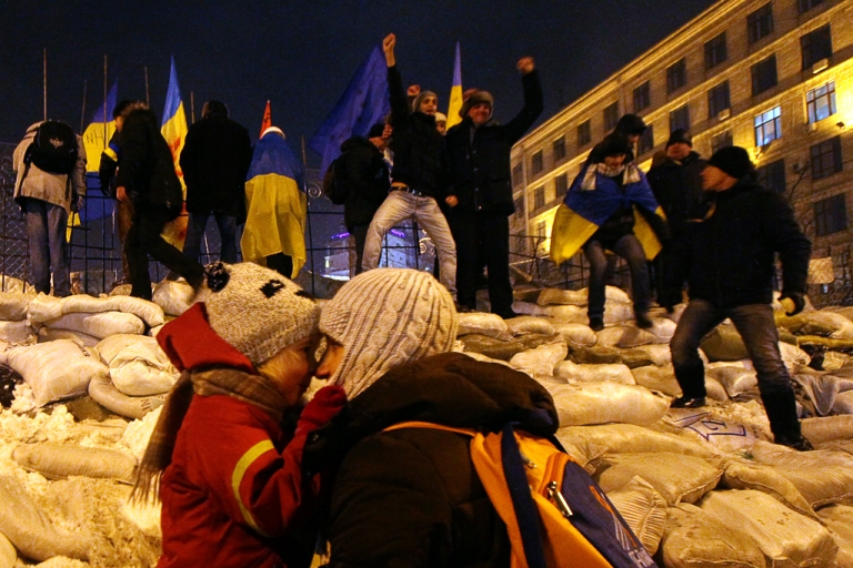 <p>Protesters stand on their newly restored barricade in Kyiv's Independence Square, late on December 11, 2013, destroyed earlier by police during a raid on the protest camp.</p>