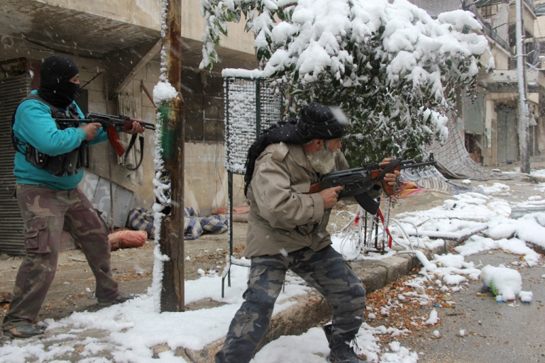 <p>Rebel fighters hold their weapons as they stand amidst snow during clashes with Syrian pro-government forces in the Salaheddin neighborhood of Syria's northern city of Aleppo on December 11, 2013.</p>