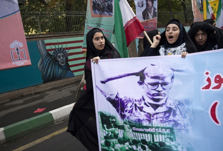 <p>Iranian schoolgirls chant slogans while holding a poster depicting an American hostage during a rally outside the former US embassy in Tehran on November 4, 2010 as they mark the 31st anniversary of the capture of the embassy by Islamist students.</p>